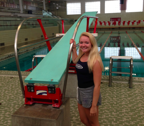 Lilly O'Neill, junior, stands poolside in her lifeguarding uniform.