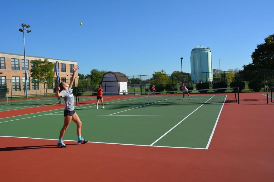 Gabrielle Rush, senior, delivers a serve at tennis practice.