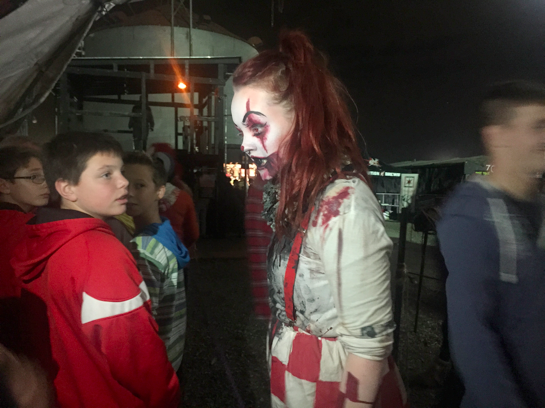 An actor dressed as a clown scares people in line.