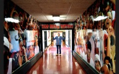 Senior Weston Berger poses in the hallway connecting to the field house, surrounded by images of cheer, something he strives to create at each of Central's student events.