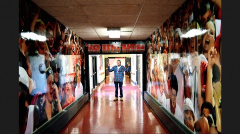 Senior Weston Berger poses in the hallway connecting to the field house, surrounded by images of cheer, something he strives to create at each of Central