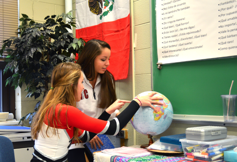 Ginger Gerhold, junior, and Taylor Gray, senior, discuss world languages week while examining cultures around the globe.
