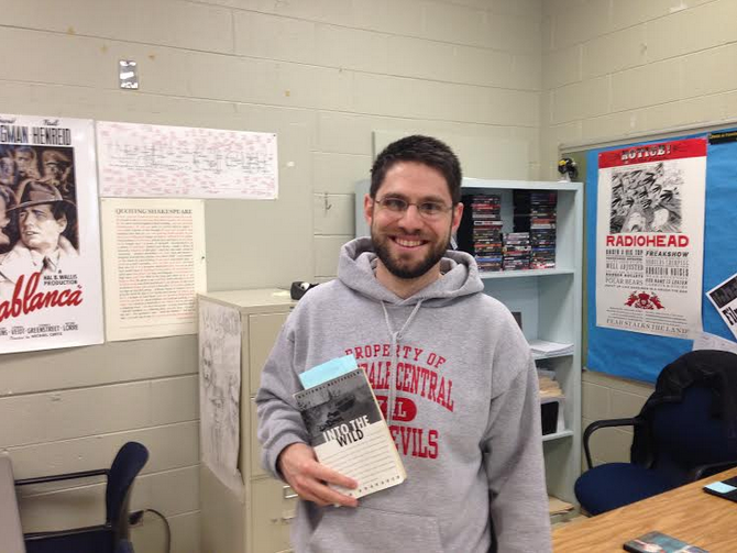 Jim DiDomenico, English teacher, poses with a copy of Into the Wild.