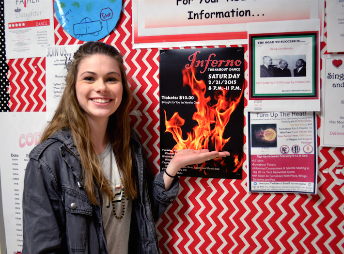 Varsity+Club+President+Beth+Schaller+poses+with+the+new+Inferno+Turnabout+poster.
