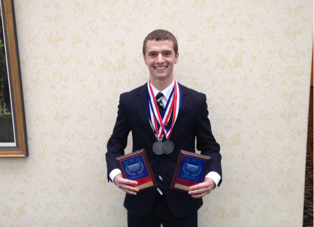 Jake+Heiser%2C+junior%2C+poses+with+his+state+medals+and+plaques.+