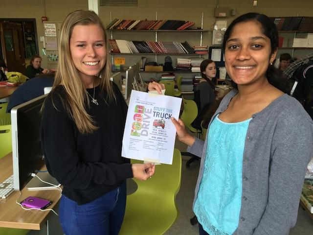 NHS members Haley Planson and Sanjana Srinivasan, seniors, proudly display the Stuff the Truck advertisement, an event that promotes donations to benefit families in need.