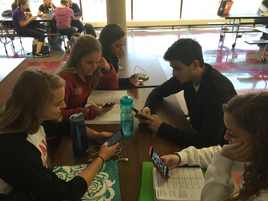 Students check their phones during study hall.