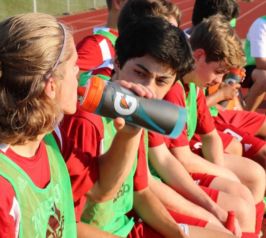 Soccer+player%2C+Wells+Doughary%2C+junior%2C+takes+a+break+from+practice+and+uses+his+catered+Gatorade+formula+to+re-hydrate.+