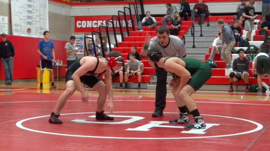 Junior Charlie Gelman begins his match against a Glenbard West opponent on Thursday, Dec. 10.