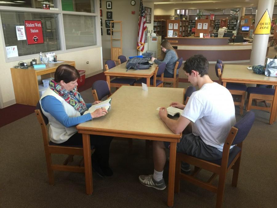 Junior JP Medick shares a table with one of the librarians as he gets ready to read for pleasure.