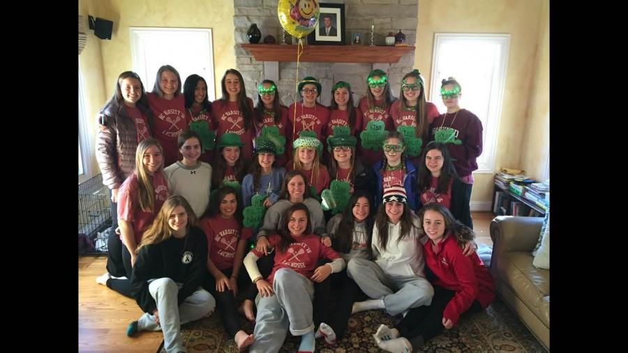 The+girls%27+lacrosse+team+poses+with+new+team+members%2C+who+are+wearing+green+outfits+as+part+of+their+welcoming+to+the+team.+