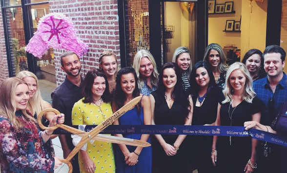 Ashley Carlevato, salon owner, cuts the ribbon during the salon's launch party on Sept. 15.