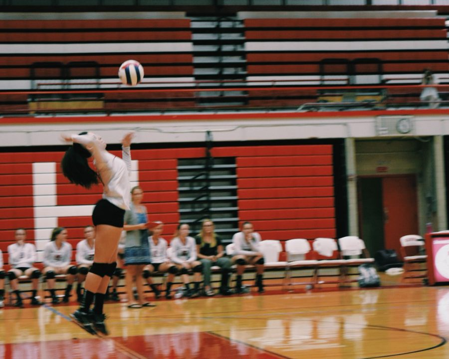 Kya Collier, sophomore, serves the volleyball against Waubonsie Valley High School on Sept. 7.