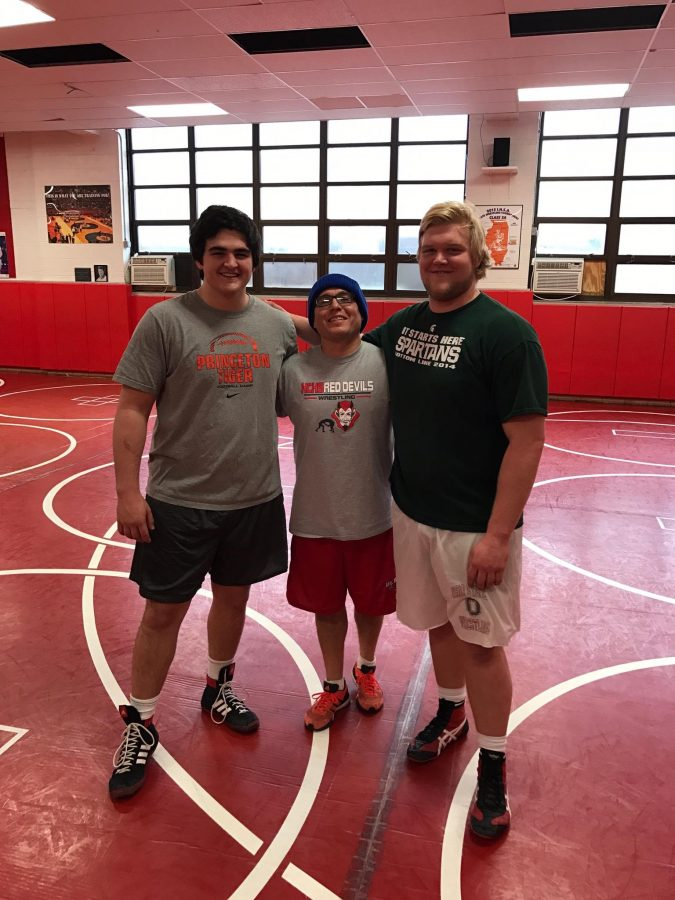 Ivanisevic, his practice partner, and Hayes pose for a photo in the Hinsdale Central wrestling room.