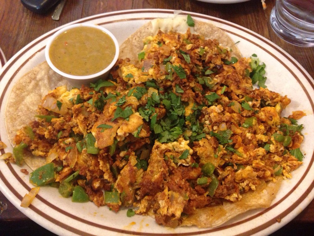 Huevos Rancheros: Soft corn tortillas with scrambled eggs, chorizo, cilantro, and salsa verde.