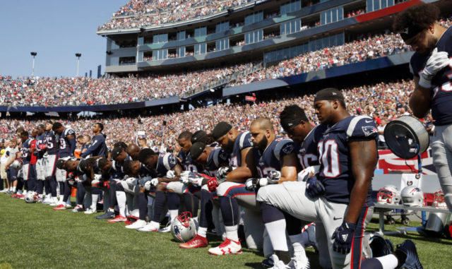 Members of the New England Patriots kneel during the National Anthem on Sunday, Sept. 24, 2017.