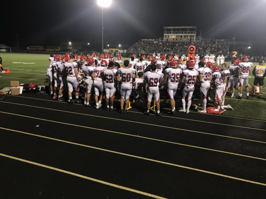 The Red Devils huddle up before the big game against Hinsdale South on their turf.