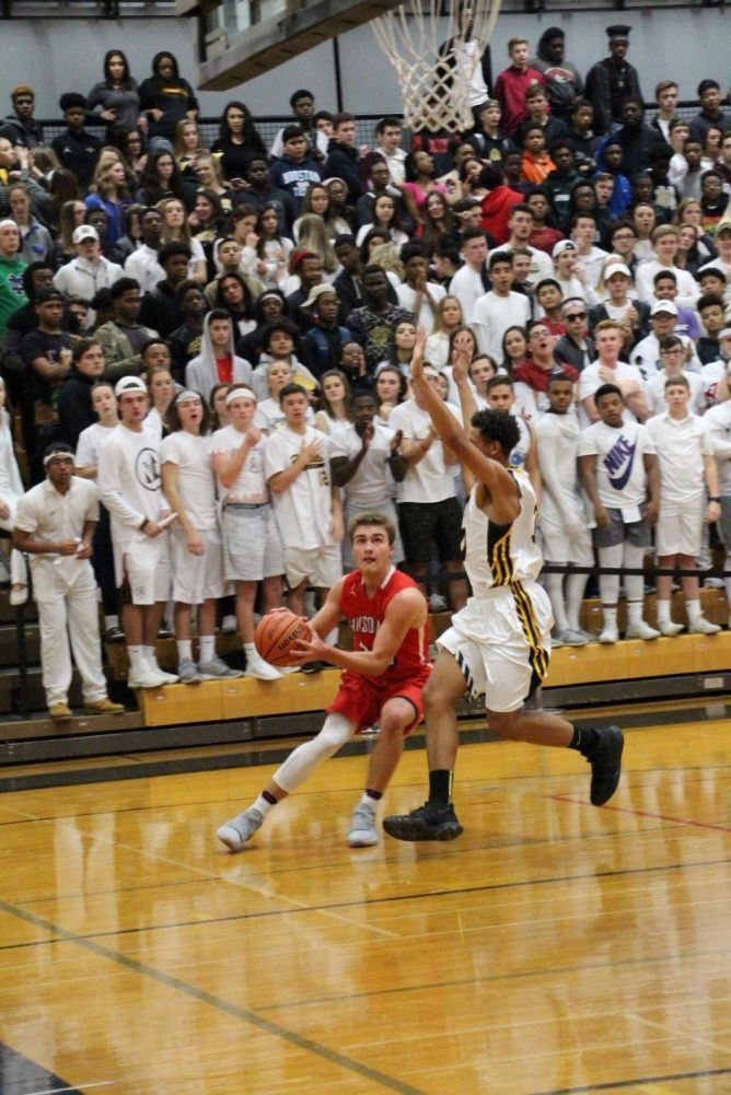 Matt Rush, junior, stares down the hoop before shooting over a Hinsdale South defender.