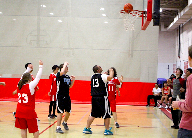 The Willowbrook Warriors attempt to make a basket while the Red Devil players try to get hold of the ball.