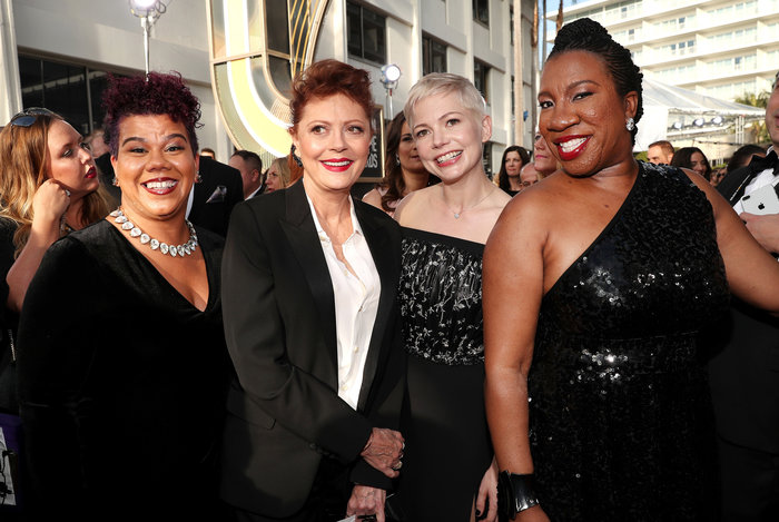 Actresses Susan Saradon (second from left) and Michelle Williams (second from right) pose with activists Rosa Clemente (far left) and Tarana Burke (Far right), all dressed in black on the Golden Globes red carpet.