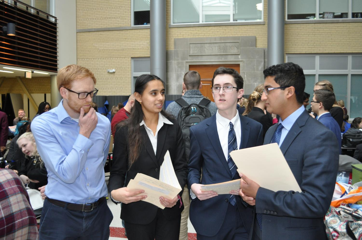 Members of the forensics team prepare with Mr. Wilbur (pictured left), coach and social studies teacher, for their events at a competition at Naperville Central High School on Sunday, Dec. 12.