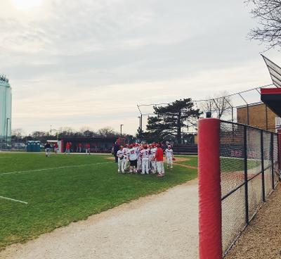 The Varsity baseball team gathers around in a team huddle in between innings to prepare for the rest of the game against Proviso West High School on April 23rd, 2018.