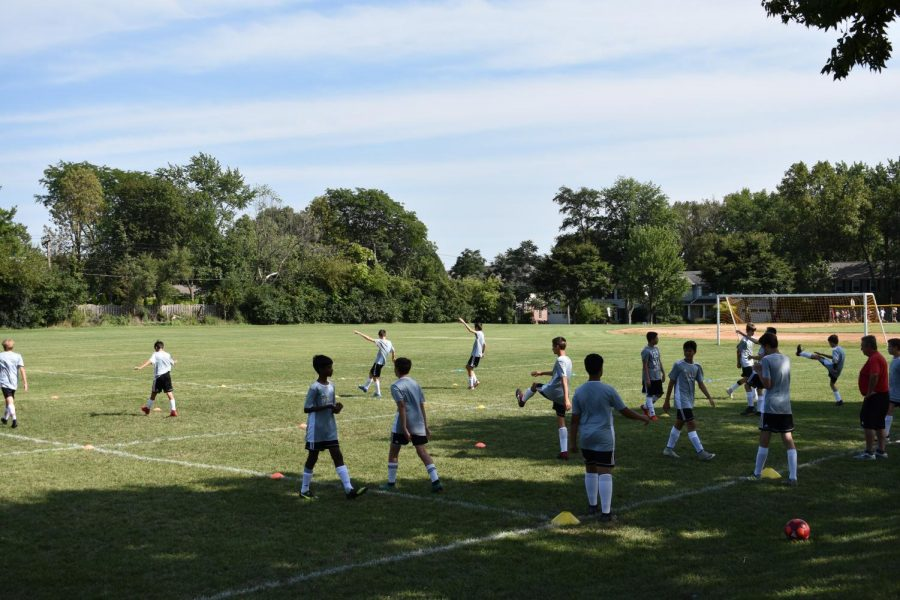 The boys' soccer teams start out their practices with a dynamic warm-up.