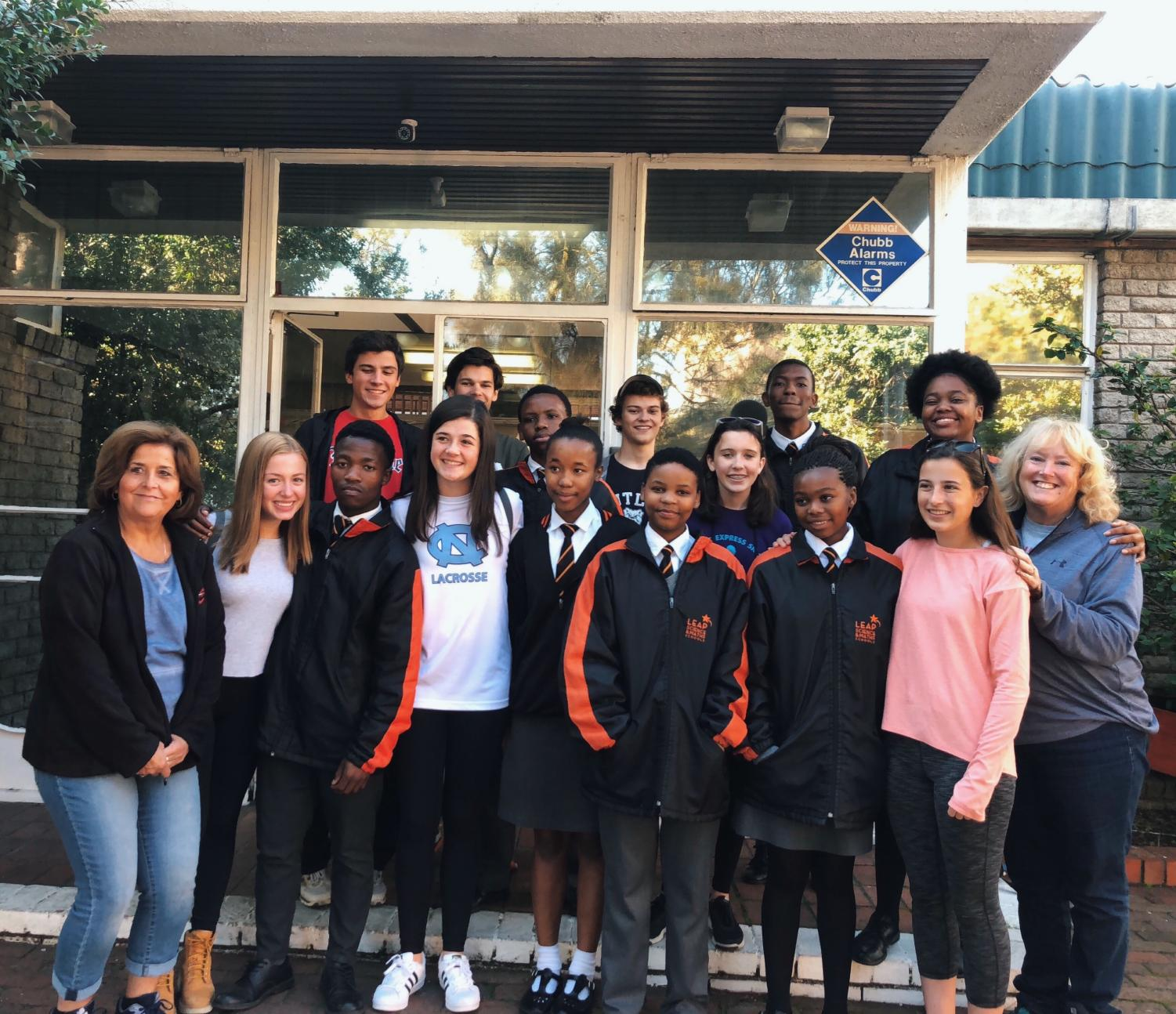 South African students and LEAP club students pose in front one of the LEAP schools that students visit this past summer in South Africa.