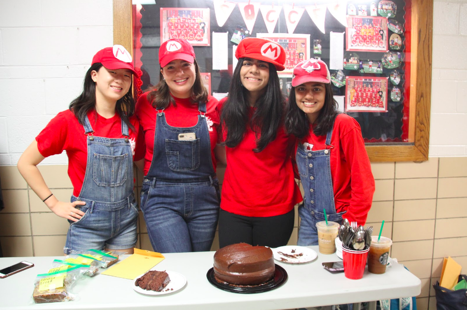 NHS members, Melissa Li, Ella Pope, Ameera Ilyas, and Shreya Sharma are depicted above dressed as Mario for the bake sale.