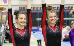 Annette Sommers, freshman, and Caroline Klobach, junior, stand next to each other, with both receiving all around athletes in the varsity West Suburban Conference meet at York Community High School on Jan. 26.