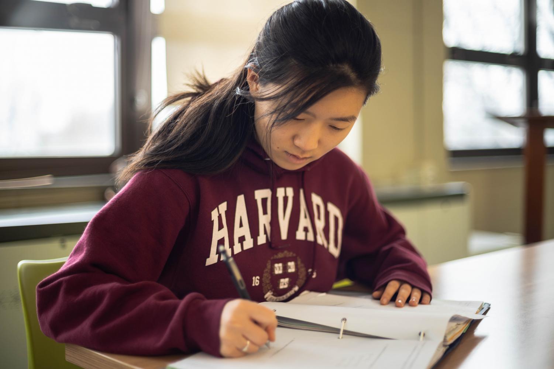 Melissa Li, senior, does homework while wearing a Harvard hoodie. Li aspired to attend an elite school since freshman year.