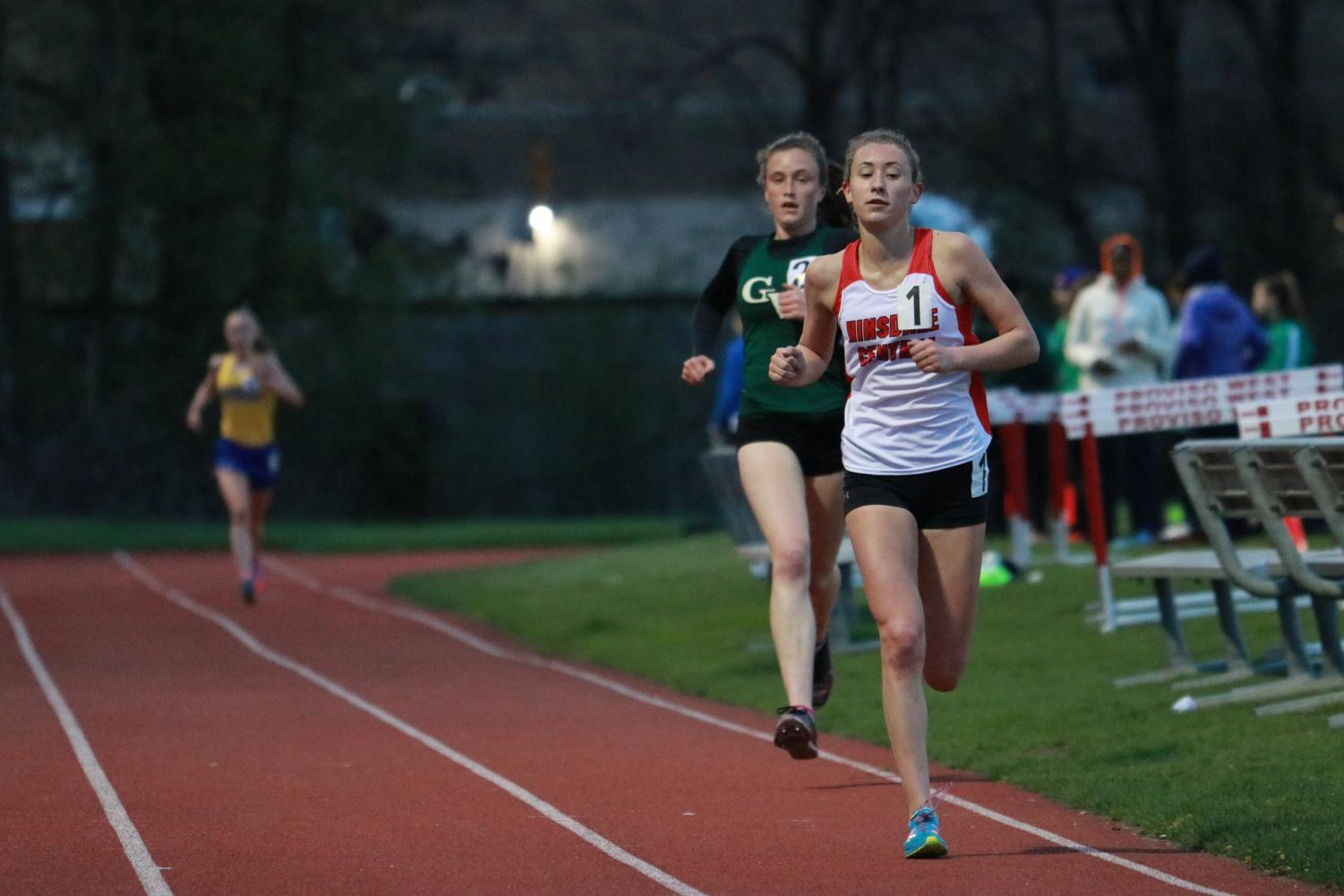 Mckenna Revord, junior, leads the 3200 meter run throughout the entire race, in front of former all state runners Katie Hohe of Glenbard West, and Sarah Barcelona of Lyons Township.