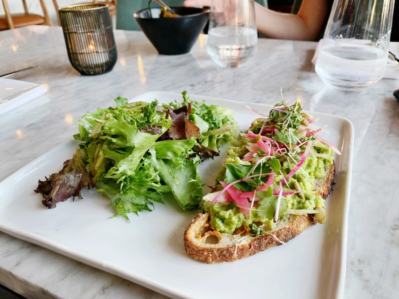 One of the items The Table at Crate serves is avocado tartines served with a side salad.