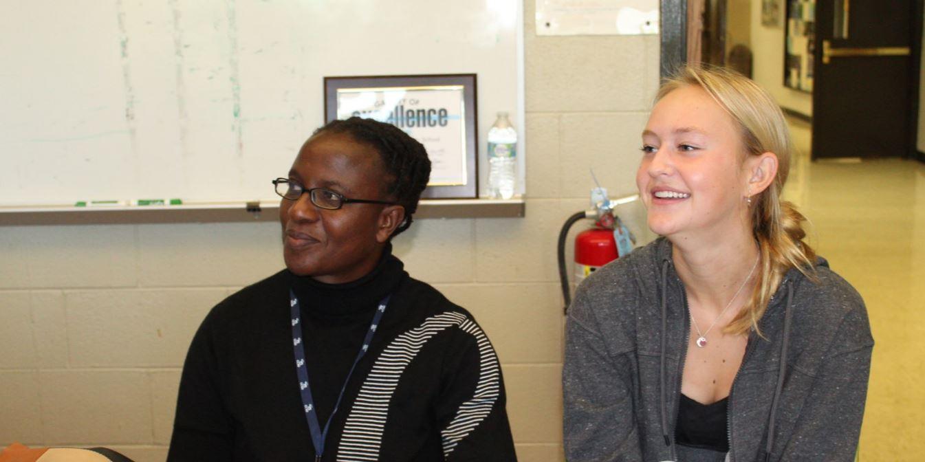 Junior Julia Paulman and visiting teacher, Bianca Chimanikire, discuss news elements in a Journalism I class.