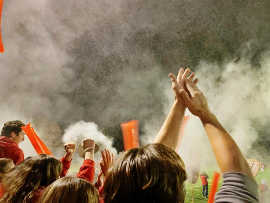 Senior social chairs Alex Ovan and Charlie Brubaker throw baby powder and confetti into the air after each Red Devil touchdown.