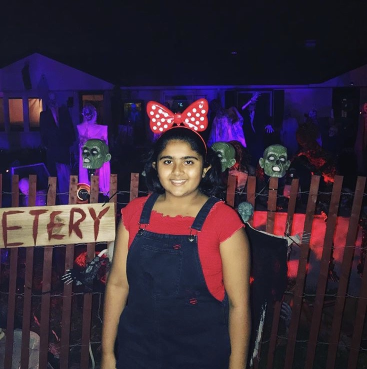 Naqiyah Anjarwala stands outside a mini haunted house that a neighbor put in their front lawn for others to come take a look.