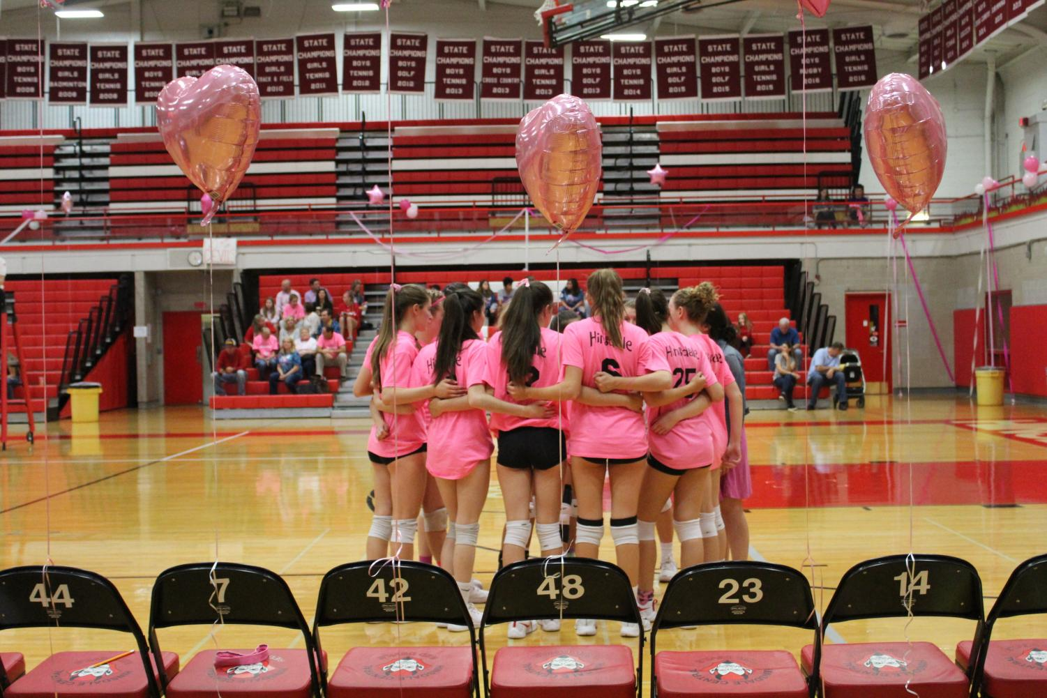 The sophomore team huddles in between sets, in front of balloons setup that decorated the event.