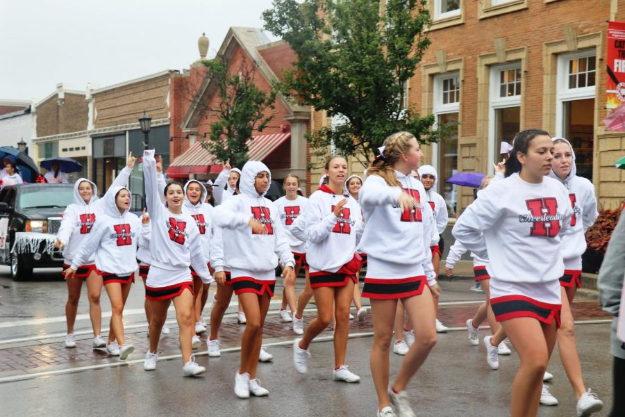 Junior Varsity Cheerleaders walk in the Homecoming Parade on Saturday, Sept. 28. Varsity Cheerleaders follow after riding in their floats.