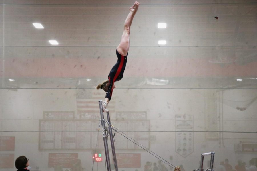 Caroline Klobach, senior, competes on the uneven bars on Friday, Nov. 22 in the Red vs White meet.