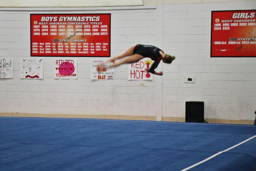 Caroline Klobach, senior, completes three tumbling passes in her floor routine during the Red vs. White meet.