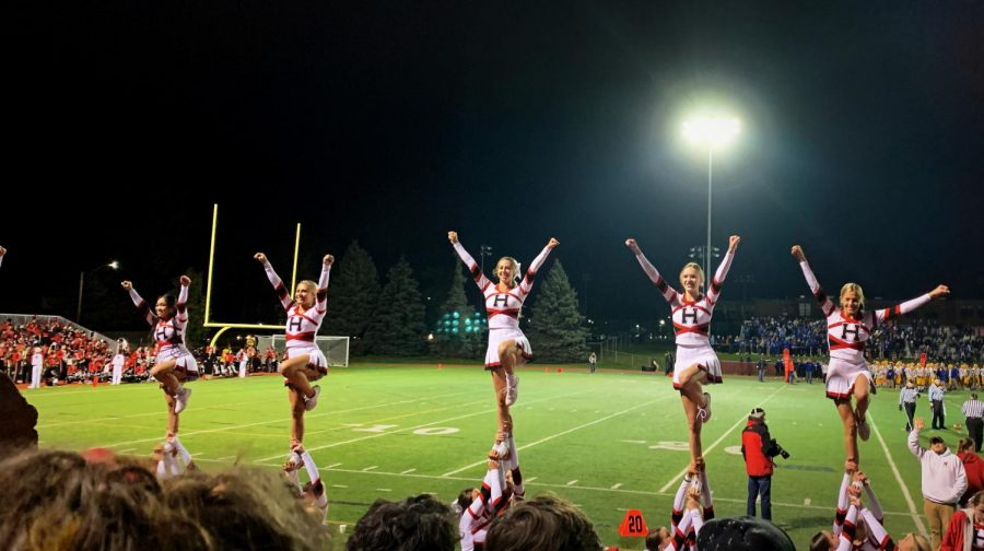 Varsity Cheerleaders hype up the crowd during the Hinsdale vs. Lyons Township football game on Oct. 25.
