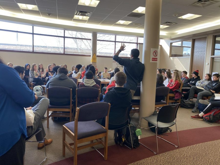 "Several students listening to the discussion raise their hands after Mr. Chokshi asks ""Who feels uncomfortable discussing diversity?"""