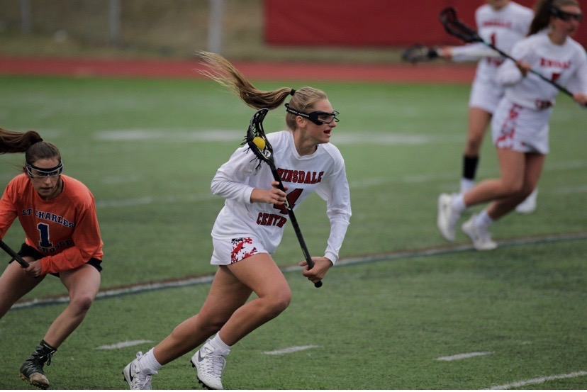 Jenna+Collignon+is+seen+sprinting+across+the+field+cradling+the+ball+in+her+lacrosse+stick+in+a+game+against+Saint+Charles+during+the+2019+season.