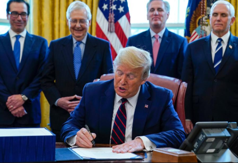 President Donald Trump, surrounded by key legislators, ratifies a $2 trillion stimulus package on March 27.