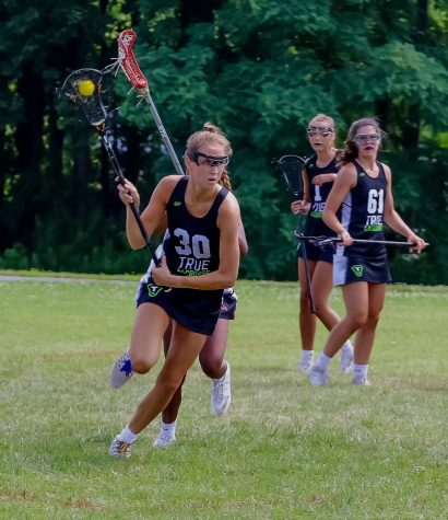 Sofija Buzelis speeds away from her teammates with ball in hand. Buzelis recently committed to playing lacrosse in college.