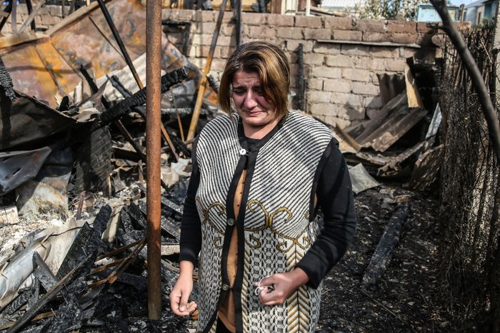 An Azerbaijani woman sees her ruined house as locals return back to the town of Tartar amidst a ceasefire on Oct. 10.