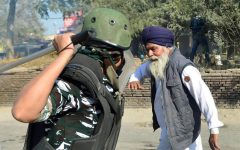 A paramilitary policeman swings his baton at an elderly Sikh man, a photograph that has become the defining image of the ongoing farmers' protest in India.