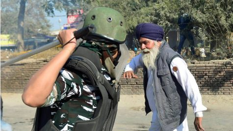 A paramilitary policeman swings his baton at an elderly Sikh man, a photograph that has become the defining image of the ongoing farmers