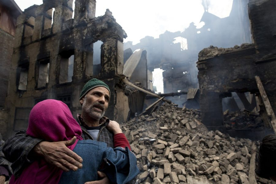 A Kashmiri woman comforts a wailing relative after his house was destroyed in a gunbattle in Tral village, south of Srinagar, Indian controlled Kashmir on March 5, 2019.