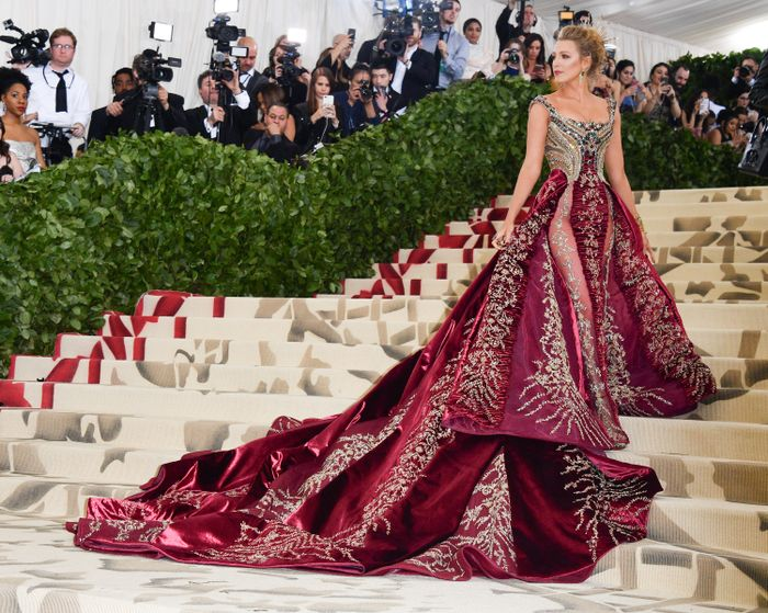 Blake Lively, American actress, attends the 2018 Met Gala and matches the color of her dress to the red carpet detailing.